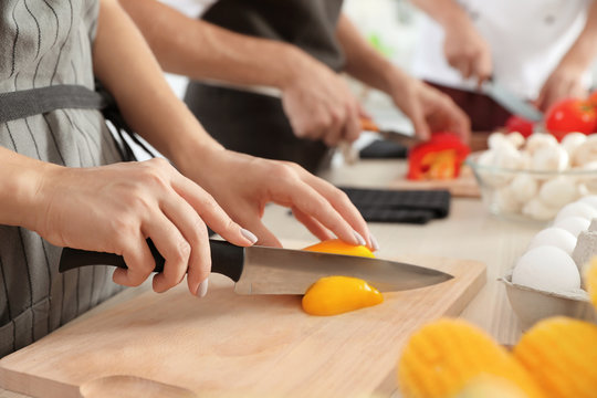 Female chef cutting paprika on wooden board at table, closeup