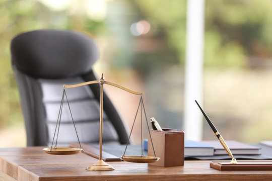 Table with scales of justice in lawyer's office