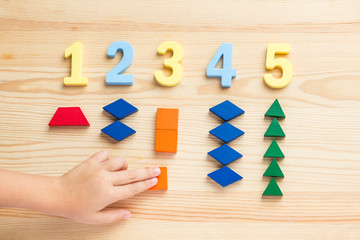 The child is studying the numbers and the account. Arranges the colored blocks to the desired numbers. Mathematics for children