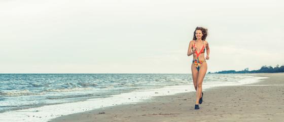 Attractive woman runs on sand beach in summer.