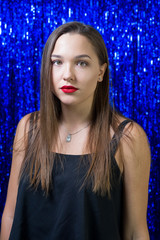 a sexy girl with red lipstick on her lips posing on the camera against the background of shiny blue sequins