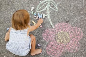 Kind malt Blume mit Straßenkreide auf Boden. Child drawing a flower with street crayon.