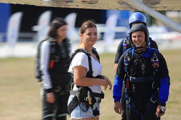 Dziewczyna i chłopak przed wejściem do samolotu ze spadochronami.
