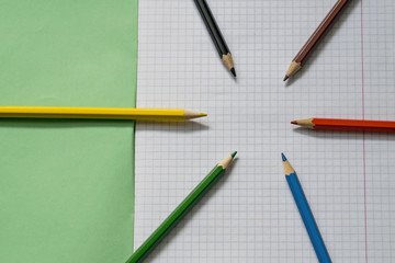 Blank paper and colorful pencils. Colored pencils on a notebook sheet. School notebook. View from above.