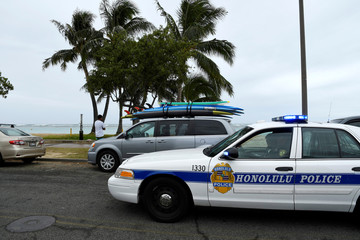 A Honolulu police car drives thru Ala Moana beach park warning beach goers as Hurricane Lane approaches Honolulu