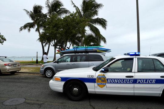 A Honolulu police car drives thru Ala Moana beach park warning beach goers as Hurricane Lane approaches Honolulu