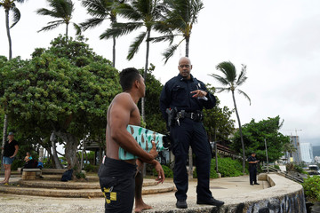 Honolulu police officer Chad Asuncion warns bodysurfer Kaimana Gomes about the water conditions as Hurricane Lane approaches Honolulu