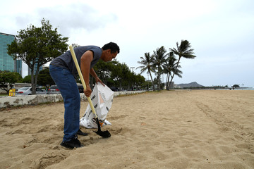 Mike Gonsalves gathers sand from a beach to fill sand bags as Hurricane Lane approaches Honolulu, Hawaii