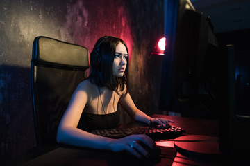 Concerned girl gamer in headphones playing network games preparing to participate in international competitions in e-sports.