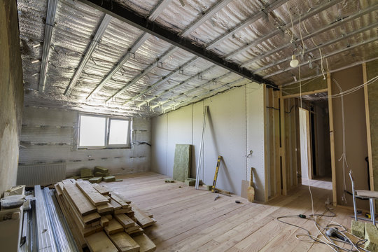 Room under construction with silver aluminum insulation foil and drywall on walls and ceiling.