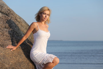 young woman by the sea in a white dress