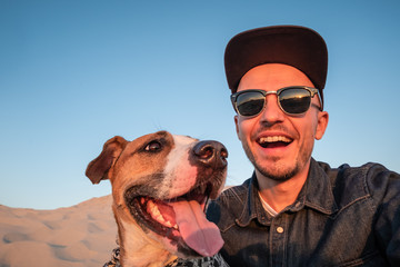 Funny best friends concept: human taking a selfie with dog. Happy young male person makes self portrait with his dog outdoors