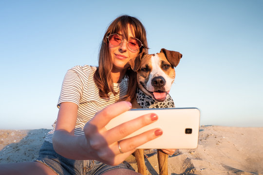 Best friends concept: human taking a selfie with dog. Young female makes self portrait with her puppy outdoors on a beach