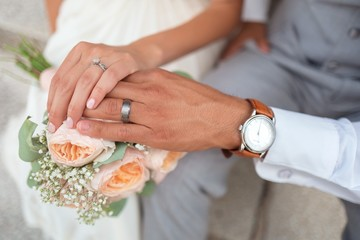 Hands of new married couple, man hand and woman hand with wedding ring, flowers and watch, polished nails