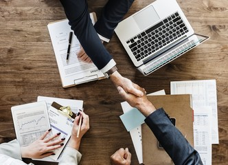Hand shaking from above, desk with laptop, contract, woman hands, male hands, suit, pens, papers, corporate, recruitment loan investment