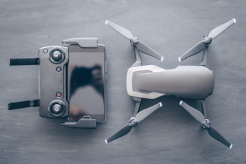 Wall Mural - A new black drone on a black table. The concept of using drones in life and industry. Top view Remote and smartphone macro Details. Copy space. Innovation photography concept. Mate color.