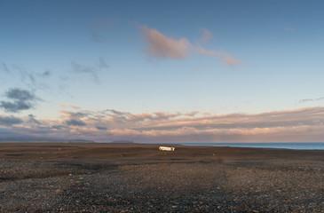 The evening sun lights up the Sólheimasandur plane wreck, which lies on a black sand beach ib Iceland.