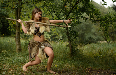 The girl in the animal skins is hunting with a spear