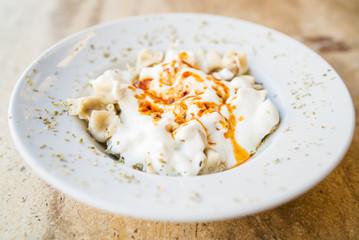 Turkish Mantı, traditional turkish food, sauce with yogurt on the turkish ravioli