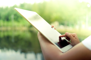 Woman hand using big tablet to do work, planning, reading in nature park.