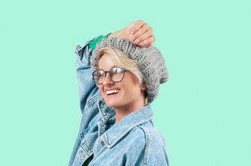 Happy beautiful girl in fashionable jeans jacket and hat on green background.