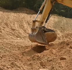 Trackhoe bucket lifting big boulder