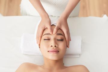 Fototapeta Smiling attractive Asian woman enjoying rejuvenating face massage in spa salon