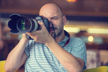 bald man holds a camera in his hands.