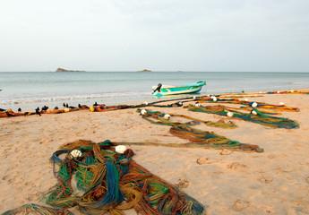 Small fishing boat next to curving fishing nets drying on Nilaveli beach in Trincomalee Sri Lanka Asia