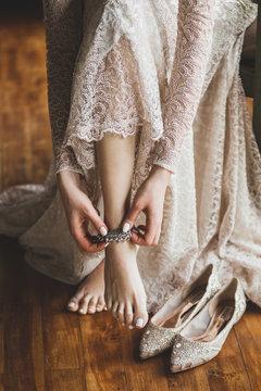 Bride wearing silver metal adornment bracelet on feet, beautiful beige lace dress