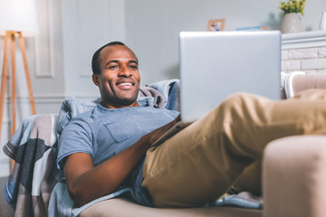 Freelance. Relaxed high-spirited man laying in the sofa while working at home
