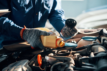 Hands of mechanic pouring a bottle of oil in car engine