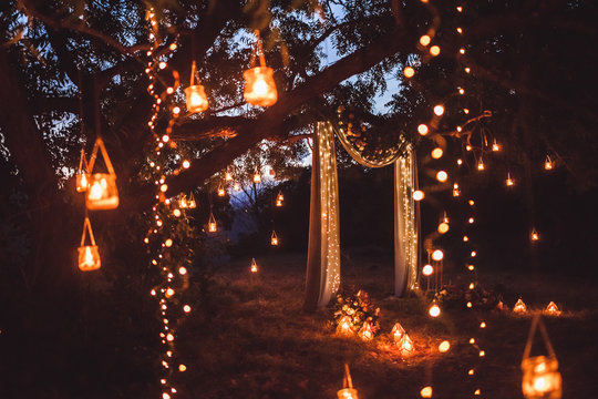 Night wedding ceremony with a lot of lights, candles, lanterns. Beautiful romantic shining decorations in twilight