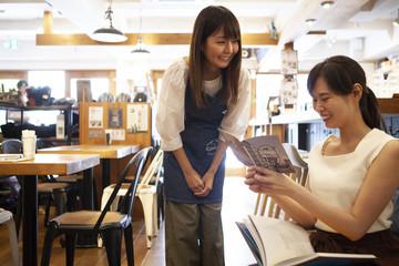 メニューを決める女性と注文を受ける店員