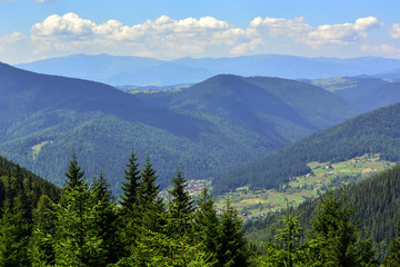landscapes of mountains covered with dense coniferous forest, against a blue sky with clouds