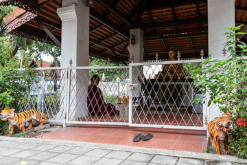Buddhist Monk Praying In Front of Statue