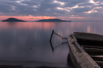 Beautiful view of Trasimeno lake (Umbria) at dusk, with a little, old boat partially filled by water, perfectly still water and a mackerel sky