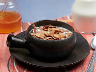 A bowl of oat bran flakes with milk and honey set on a red napkin, on a blue tablecloth, with a jar of honet and a jug of milk