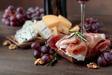 Prosciutto with various cheeses , grapes and  walnuts .