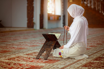 Young muslim woman praying in mosque with quran Wall mural