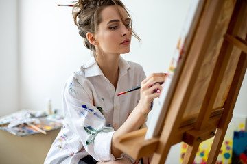 Closeup of beautiful woman painting on canvas in studio