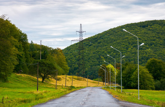 country road in mountains. lights and power line tower along the road
