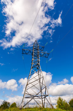 power line tower on the hill. view from below. beautiful blue sky with clouds