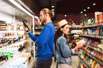 Young beautiful couple standing back to back thoughtfully choosing products while spending time in modern supermarket