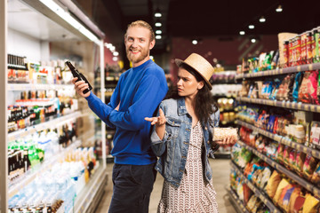 Young smiling guy happily looking in camera holding beer in hand while girl thoughtfully looking at him in supermarket