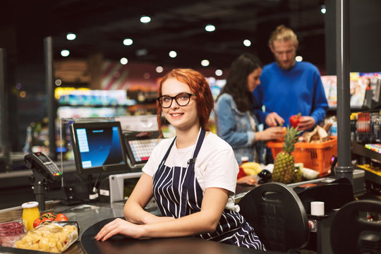 Young smiling cashier in eyeglasses and striped apron happily looking in camera while working in modern supermarket with customers on background