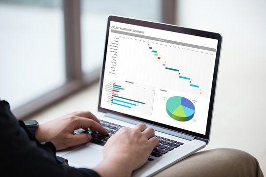 Man working with excel project dashboard on laptop / computer at office