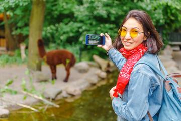 Woman taking photo of Llama grazing at feeding time in Zoo
