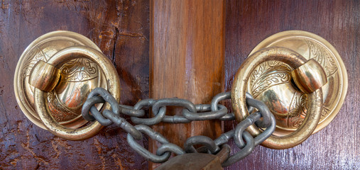 Closeup of two antique copper ornate door knockers over an aged wooden ornate door closed with rusted chain, Eyup Sultan Mosque, Istanbul, Turkey