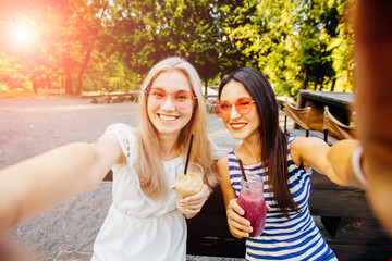 Two excited hipster girls, women, friends in pink sunglasses the blonde and the brunette taking selfie, drink cocktails at modern outdoor cafe on the green park. Wearing in striped and white dress.